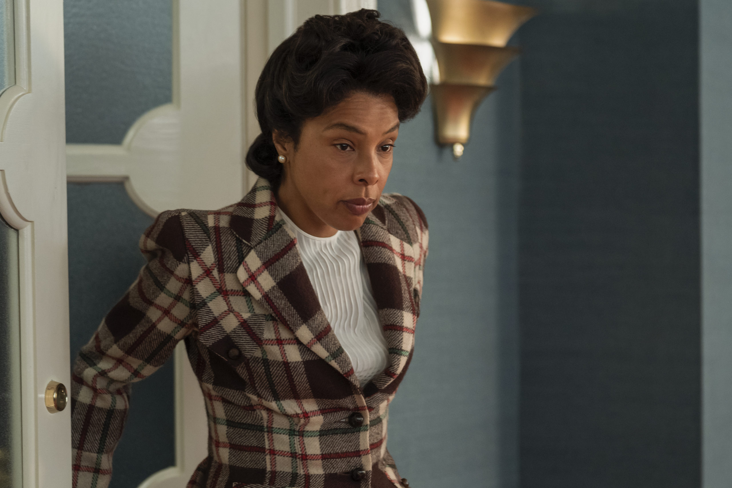 Cena da série Ratched. A cena mostra Sophie Okonedo, uma mulher negra, olhando para baixo com expressão distante. Ela usa roupas com estampa de xadrez marrom.