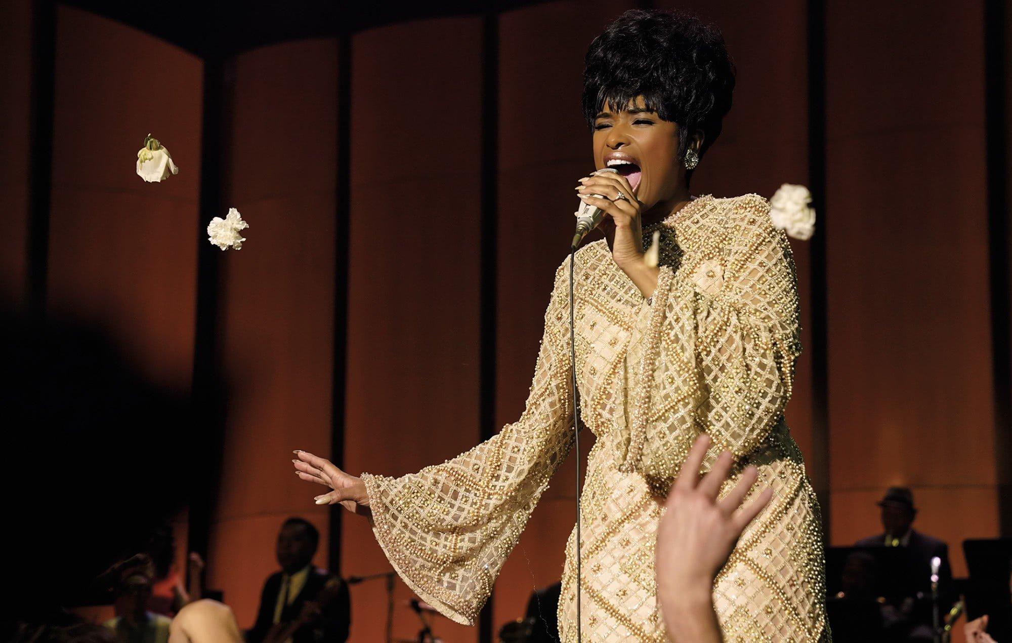 Cena do filme Respect, que mostra Aretha, personagem de Jennifer Hudson, cantando em um palco iluminado. Ela é negra, alta, tem cabelo preto e usa um vestido claro, segurando o microfone com a mão esquerda.