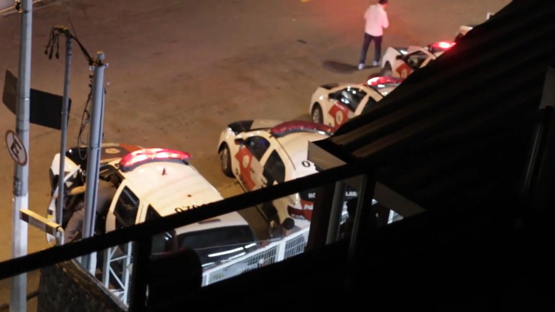 """Cena do documentário Rua Augusta, 1029. A imagem é capturada à noite, da janela do prédio ocupado pela Frente de Luta por Moradia (FLM), por onde vemos carros de polícia enfileirados lado a lado, com as sirenes ligadas. No primeiro carro, localizado do lado de um poste com uma placa de """"proibido estacionar"""", um policial procura algo dentro da viatura."""