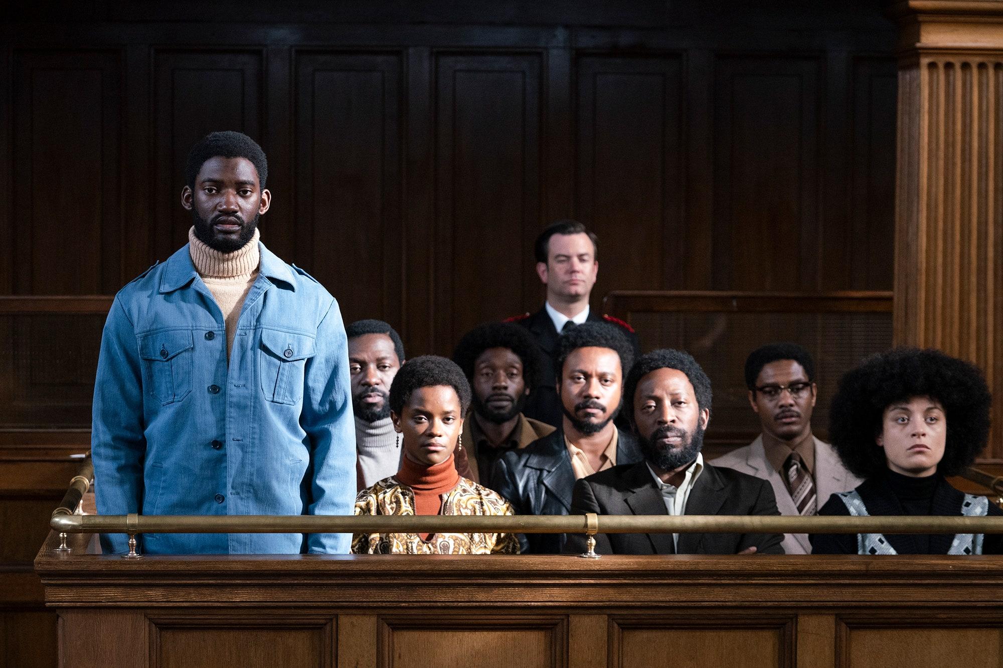 Cena do filme Mangrove, parte da antologia Small Axe. A cena mostra um homem negro, vestindo blusa jeans, em pé no tribunal. Atrás dele, estão sentadas uma porção de pessoas, todas negras, olhando para frente.