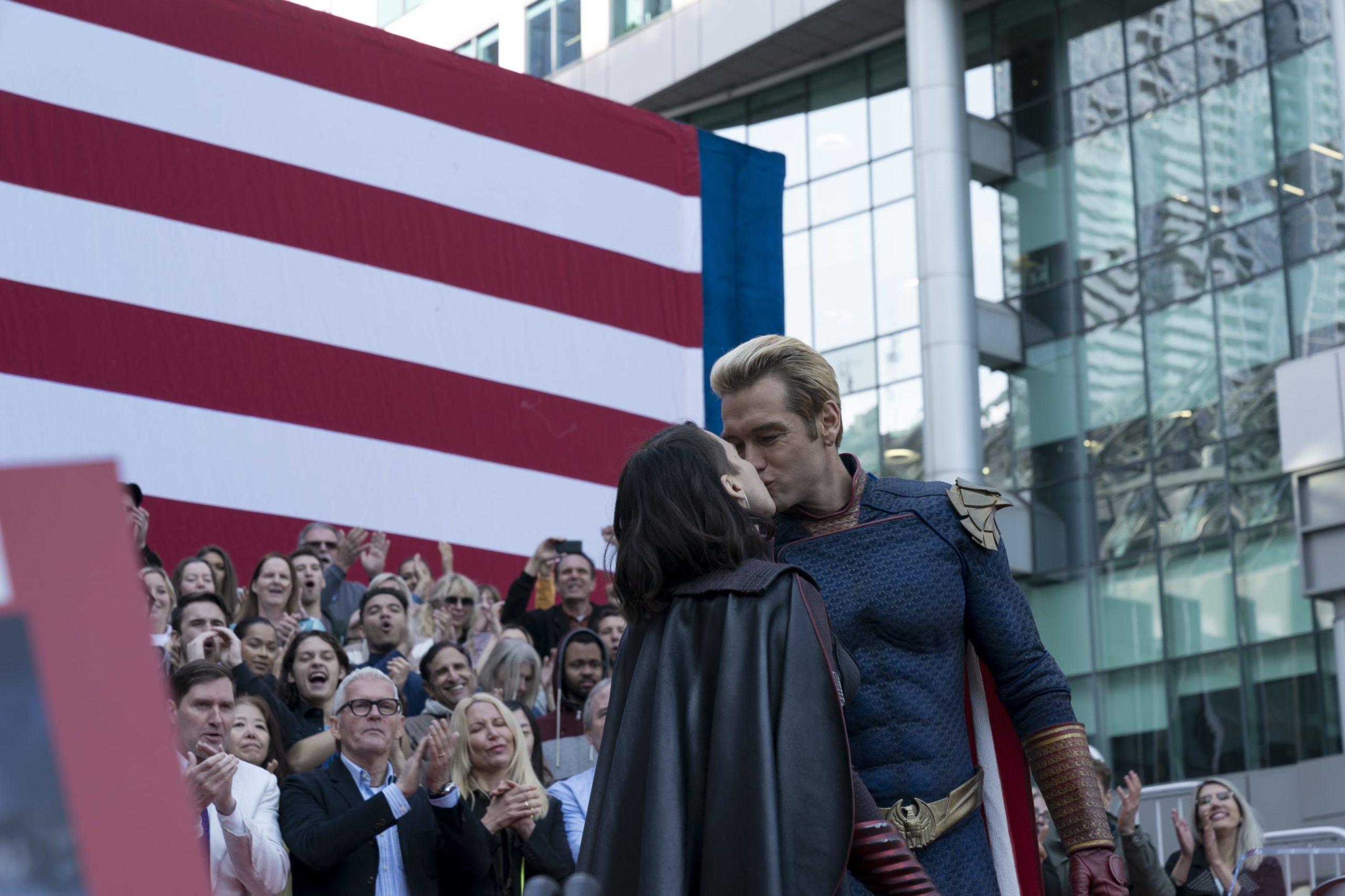 Cena da segunda temporada de The Boys. Ao centro da imagem, em frente a uma bandeira dos Estados Unidos e a uma arquibancada lotada de gente aplaudindo e sorrindo, vemos as personagens Tempesta e Capitão Pátria, vestindo seus uniformes de herói, se beijando.