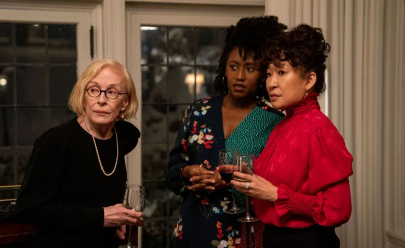 Cena da série The Chair. Na imagem, Joan, Yaz e Ji-Yoon estão reunidas em uma sala tomando vinho, enquanto as três observam algo do outro lado da cena. Joan é uma mulher idosa branca, com cabelos loiros em corte chanel, usa óculos de aro redondo, uma blusa preta e colar de pérolas. À sua direita está Yaz, uma mulher negra de cabelos cacheados semi presos que usa um vestido estampado de azul floral e verde. À direita de Yaz está Ji-Yoon uma mulher asiática com cabelos presos em um coque acima da cabeça, e blusa pink de gola alta e mangas compridas. A expressão das mulheres é de curiosidade. Ao fundo há duas grandes janelas de vidro e cortinas brancas.