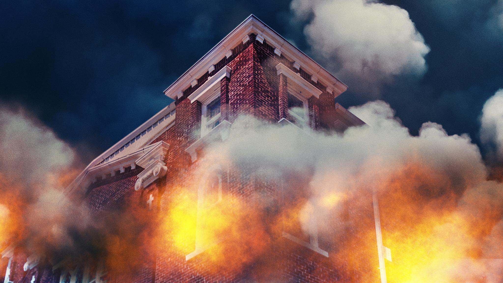 Cena do documentário Tulsa Burning: The 1921 Race Massacre. A imagem mostra a esquina de um prédio de tijolos vermelhos em chamas, visto de cima para baixo. O céu é azul escuro e é tomado por uma fumaça cinza, que surge do fogo que sai de dentro das janelas brancas do prédio.