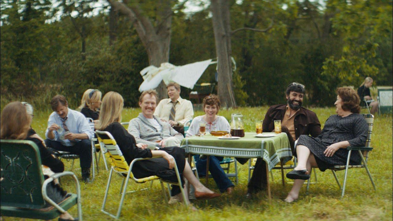 Cena do filme Tio Frank. Na imagem, em um jardim, vemos várias pessoas sentadas em cadeiras espalhadas pelo espaço. Ao centro, sentados em volta de uma mesa com copos e bebidas, vemos, da esquerda para a direita, a cunhada de Frank, Frank, Betty, Wally e a mãe de Frank rindo.