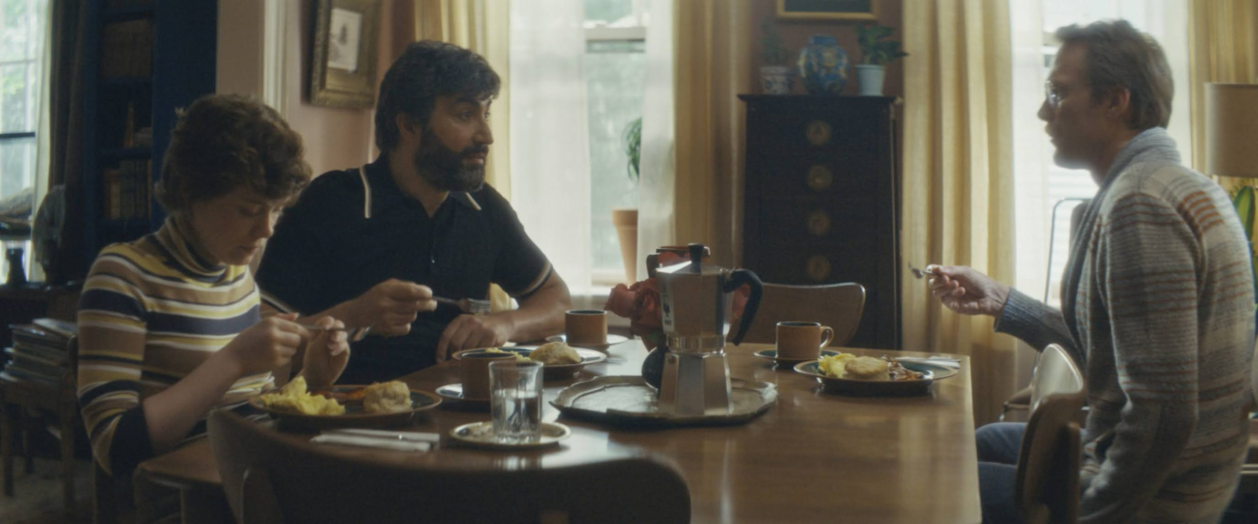 Cena do filme Tio Frank. Na imagem, sentados ao redor de uma mesa de café da manhã posta, em uma sala de estar de uma casa, vemos, do lado esquerdo, Betty, uma mulher branca, de cabelos ruivos curtos e enrolados, aparentando ter cerca de 15 anos, vestindo uma blusa listrada de gola alta; Wally, um homem muçulmano, de cabelos e barba pretos, aparentando ter cerca de 40 anos, vestindo uma camiseta polo preta; e, do lado direito, Frank, um homem branco, de cabelos e bigode loiros, aparentando ter cerca de 40 anos, vestindo um casaco cinza listrado
