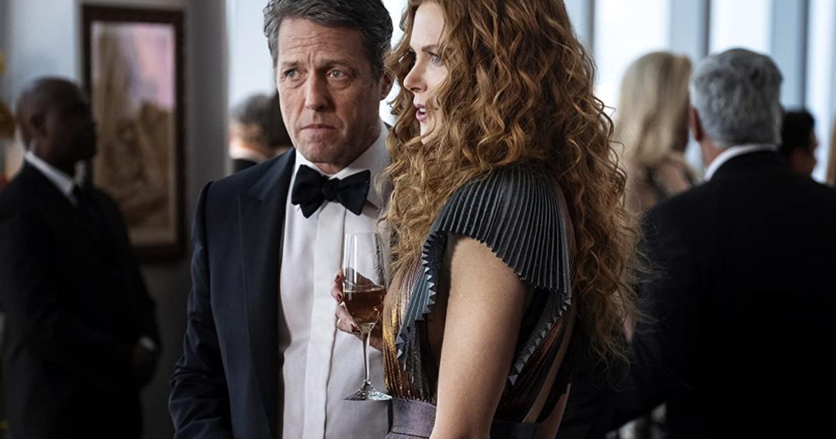 Cena da minissérie The Undoing. A cena mostra Hugh Grant, branco e de smoking, e Nicole Kidman, branca e ruiva, de vestido branco e preto, de pé, em uma festa chique. Está de dia e ela segura uma taça de champanhe.