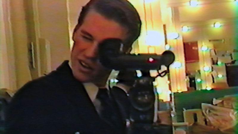Cena do filme Val exibe uma gravação antiga na qual um homem branco, com cabelo curto penteado para a esquerda, segura uma câmera grande e filma um espelho. Vemos que ele está num camarim de um teatro. Ao fundo, há um espelho iluminado por lâmpadas na moldura e uma penteadeira cheia de vários objetos em cima.