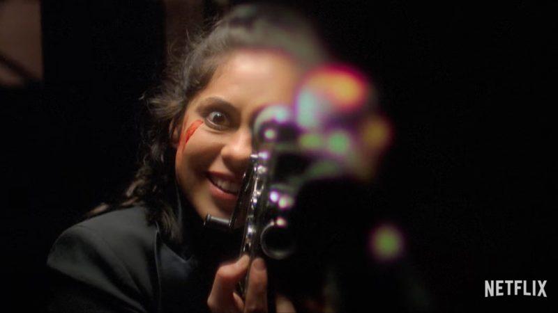 Cena da minissérie Vingança Sabor Cereja. Lisa Nova (Rosa Salazar) a câmera com um sorriso maníaco, filmando-a com uma outra câmera antiga, segurando-a com as duas mãos e pressionando ela contra o lado esquerdo de seu rosto. Lisa é branca, tem cabelos pretos puxados para trás com alguns fios escapando, usa uma jaqueta preta que está fora de foco. A câmera em seu rosto está distorcida e fora de foco, e o cenário atrás dela está obscurecido.