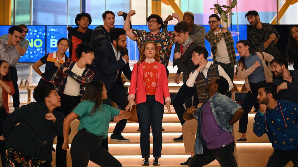 Cena da segunda temporada de Zoey e sua Fantástica Playlist. Vemos uma mulher ruiva parada nas escadas de uma pequena arquibancada. Ela olha assustada para as várias pessoas que cantam e dançam ao seu redor. Ela veste um suéter vermelho com estampa de flores brancas por baixo de um paletó rosa. Usa calça jeans, sapatos pretos e carrega uma bolsa pequena no ombro direito.