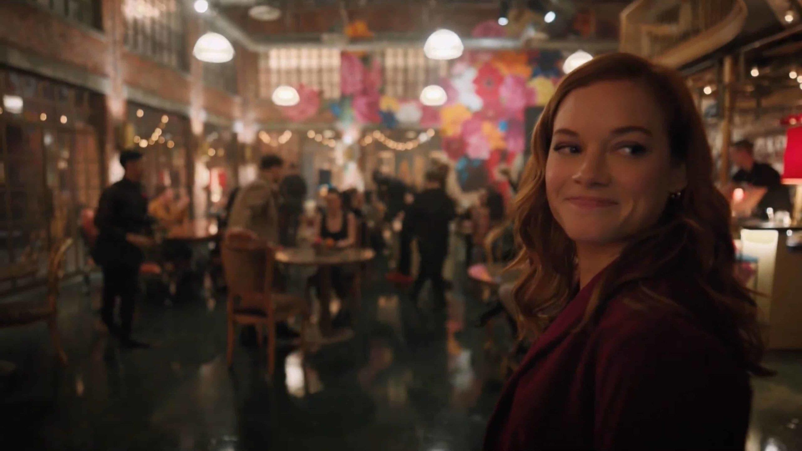 Cena da segunda temporada de Zoey e sua Fantástica Playlist. Vemos uma mulher branca e ruiva dentro de um restaurante movimentado, durante a noite. Ela veste um paletó vinho e olha para trás. Atrás dela, à direita, há um bar. As paredes do local tem tijolos expostos e uma delas foi pintada com várias flores, de cores diferentes.