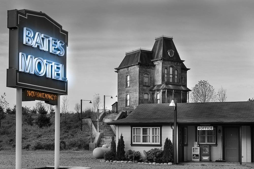 """Cena da série Bates Motel. Na imagem, vemos o Motel Bates, pequeno e simples, com paredes feitas com ripas de madeira, uma janela na lateral, com algumas plantas embaixo, e um pouco mais à direita, uma placa escrita """"office"""", mostrando a direção do escritório dos administradores do local. Há também um pequeno poste de luz próximo à janela, que no momento, está aceso. Do lado esquerdo, há uma escada que sobe para uma pequeno barranco, e direciona para a casa da família Bates, também antiga e simples, toda feita em madeira. Logo mais à frente, há uma placa com os dizeres iluminados em neon na cor azul """"Bates Motel"""", e abaixo, em laranja está escrito """"No Vacancy"""" (ou, """"Sem Vagas""""). A imagem é toda em preto e branco, com exceção da placa. O ambiente é ao ar livre, e está de noite."""
