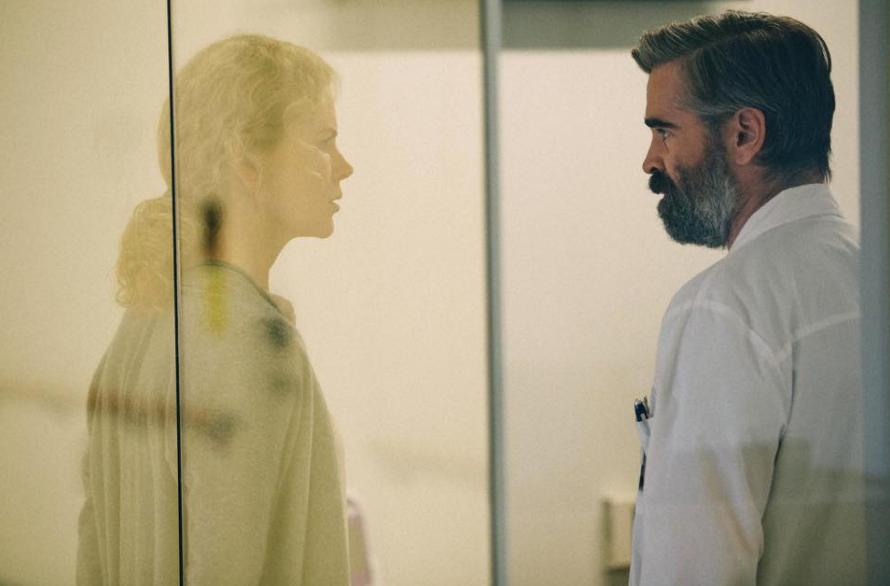 Cena do filme O Sacrifício do Cervo Sagrado. A personagem Anna, uma mulher loira, está ao lado esquerdo com mais claridade e o personagem Steve, um homem branco, está vestido com um jaleco médico do lado direito com menos claridade. Ambos estão se encarando pela porta de vidro do hospital.