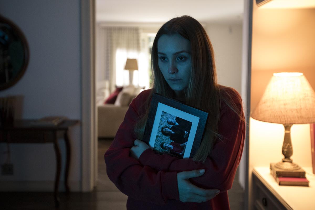 Cena do filme A Menina que Matou os Pais. Nela, vemos Carla Diaz, branca e loira, de roupa vermelha, abraçando um porta retrato. A iluminação é azulada e ela tem uma expressão vazia no rosto.