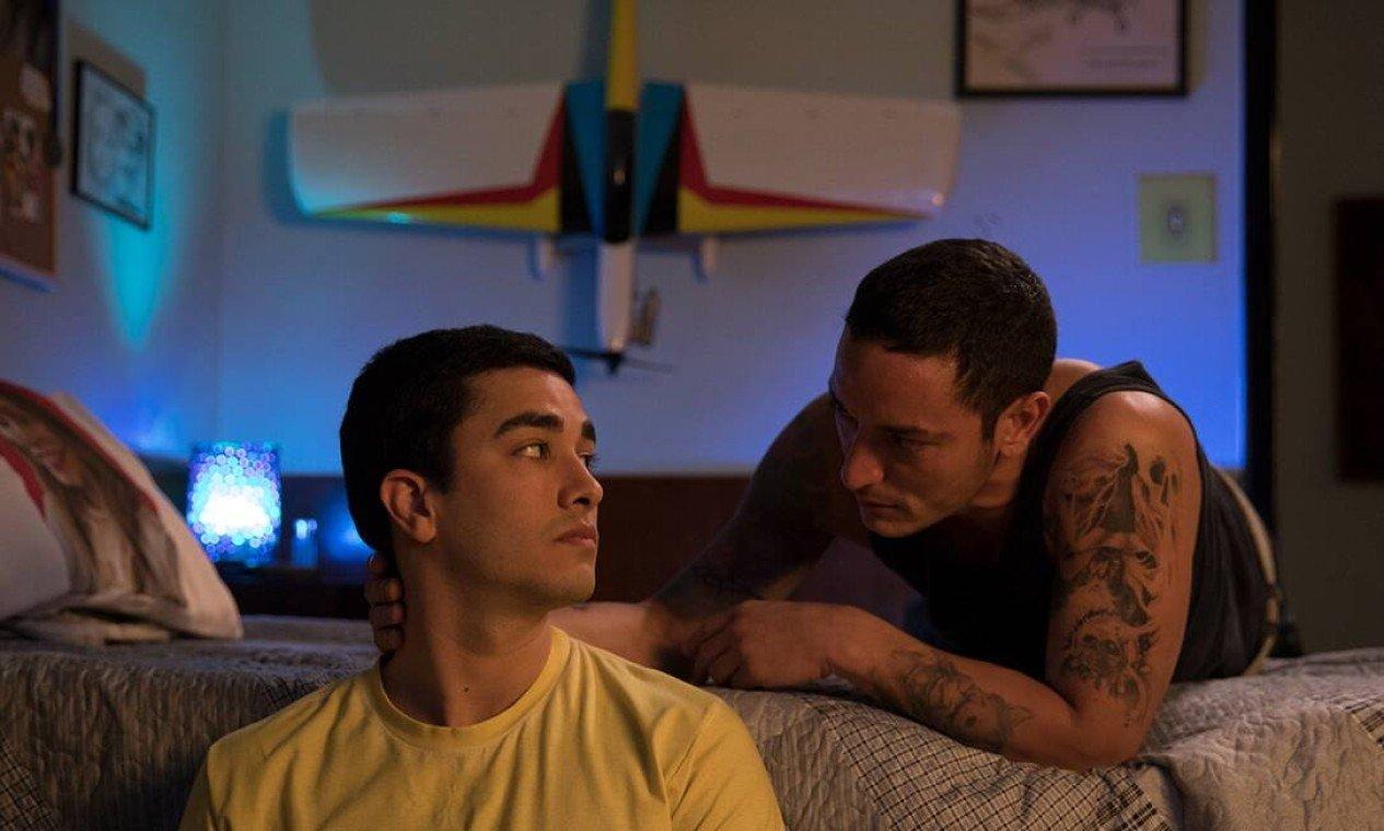 Cena do filme A Menina que Matou os Pais. Nela vemos Daniel e Cristian Cravinhos, dois homens brancos e adultos, no quarto. Daniel está no chão e Cristian está deitado na cama, com a mão na nuca do irmão.