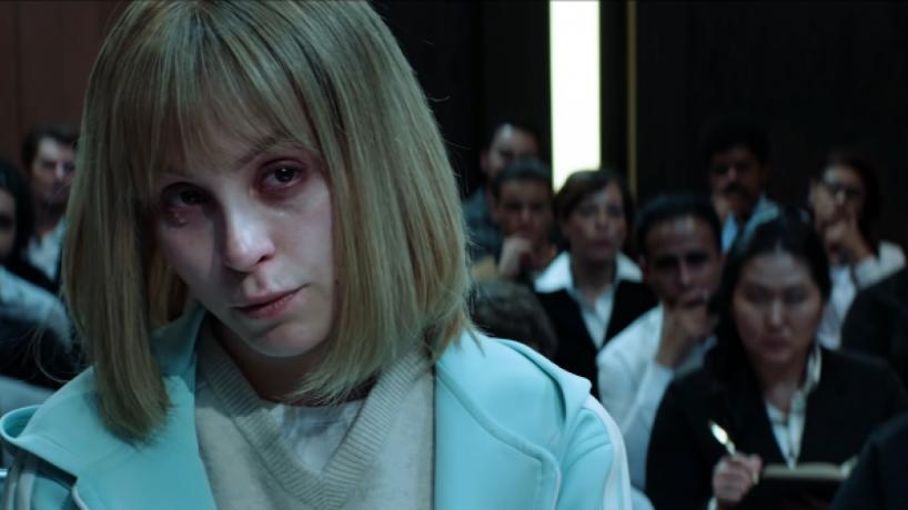 Cena do filme A Menina que Matou os Pais. Nela vemos Carla Diaz no banco do tribunal. Ela é branca, loira e usa uma blusa azul bebê.