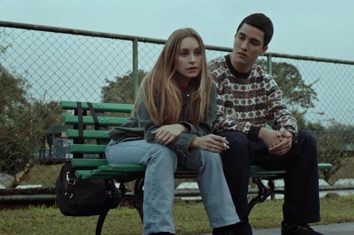 Cena do filme A Menina que Matou os Pais. Nela vemos o casal principal, Suzane e Daniel, sentados em um banco de praça. Está de dia, ela está apoiada para frente, fumando, e ele está olhando para ela.