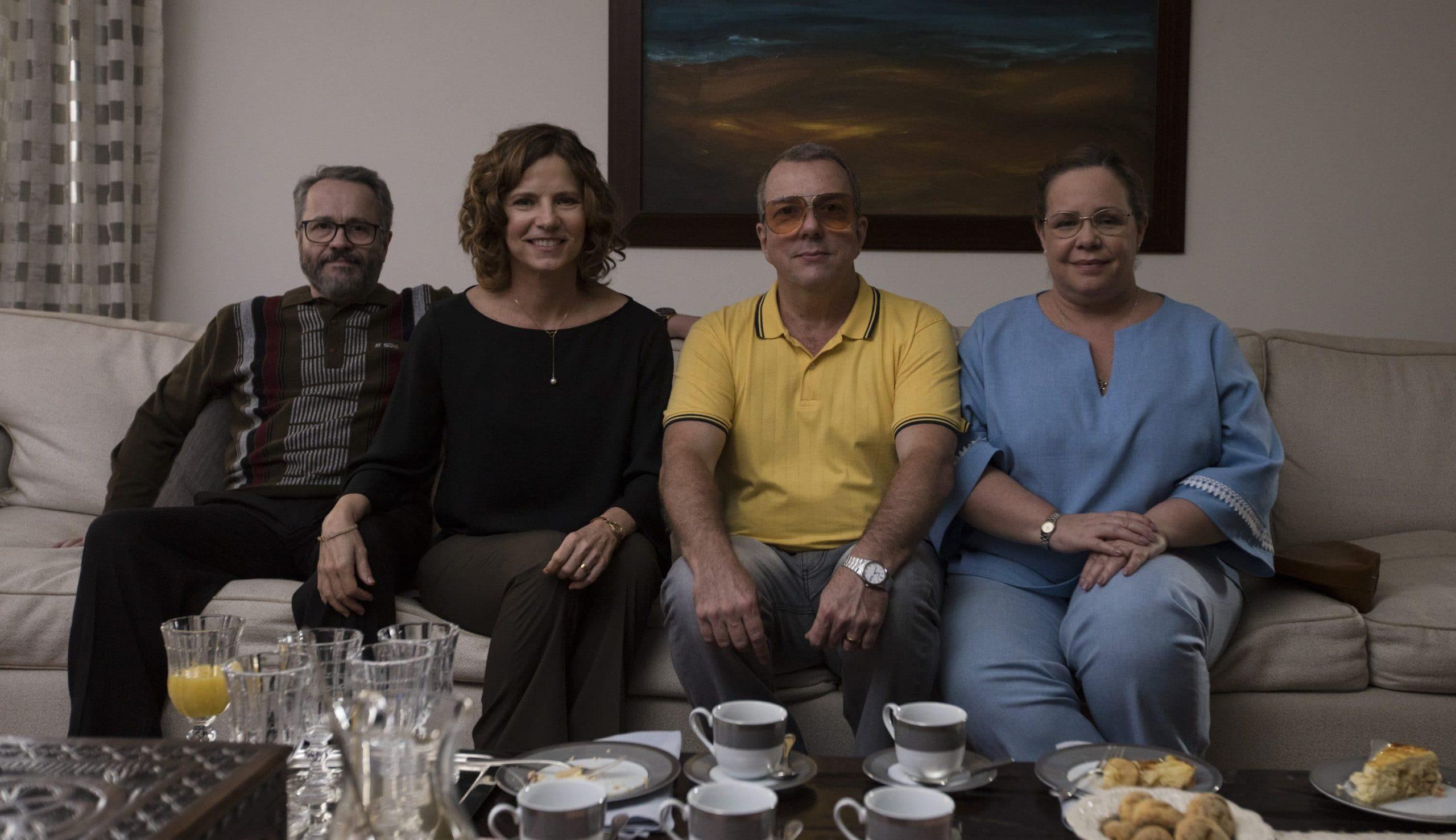 Cena do filme A Menina que Matou os Pais. Nela vemos 4 pessoas brancas sentadas em um sofá. Todas são adultas, perto da meia idade. Da esquerda para direita estão Manfred, Marísia, Astrogildo e Nadja.