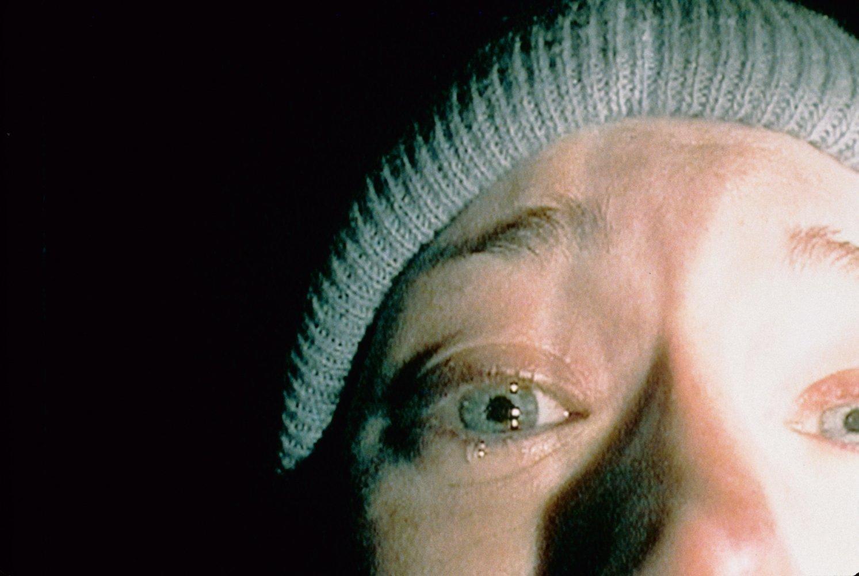 A imagem mostra Heather Donahue com uma touca cinza. O foco da imagem é o rosto de Heather, uma mulher branca, de olhos azuis que aparenta estar assustada. Ela está chorando com a câmera focada em seu olho direito (esquerdo para quem lê a imagem). Heather está com as sobrancelhas arregaladas. O fundo da imagem é preto.