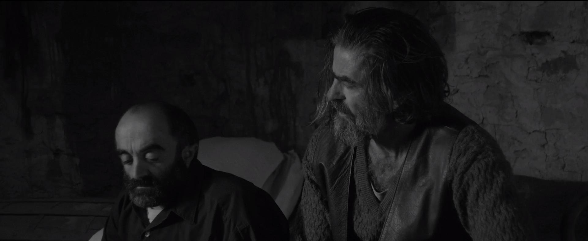 Cena do filme Armugan, em preto e branco. Vemos um homem baixinho, careca e barbudo sentado em uma cama. À esquerda, vemos um homem com cabelo comprido, barba grande e alto também sentado na cama. Ambos são brancos e estão na meia idade. Vestem roupas adequadas para o clima da região montanhosa.