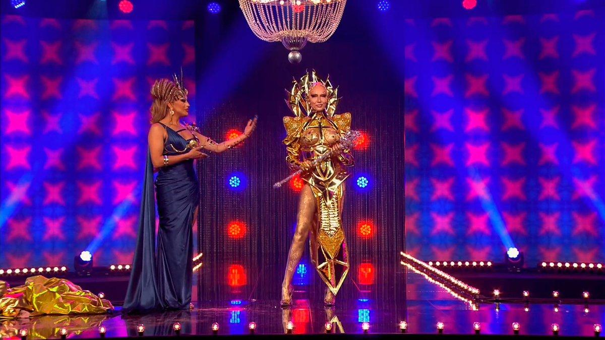 Cena de Drag Race Holland. A cena mostra Envy Peru coroando Vanessa van Cartier, que usa uma roupa dourada e segura um cetro prateado nas mãos.