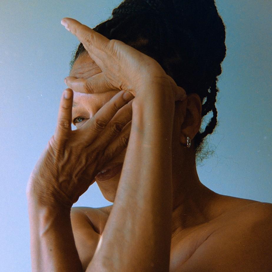 Capa do CD Delta Estácio Blues. A cantora Juçara Marçal está no centro da fotografia, sobre um fundo azul. As mãos dela estão dispostas sobre a face de forma que só conseguimos ver um dos olhos, cabelo, parte da boca e orelha.