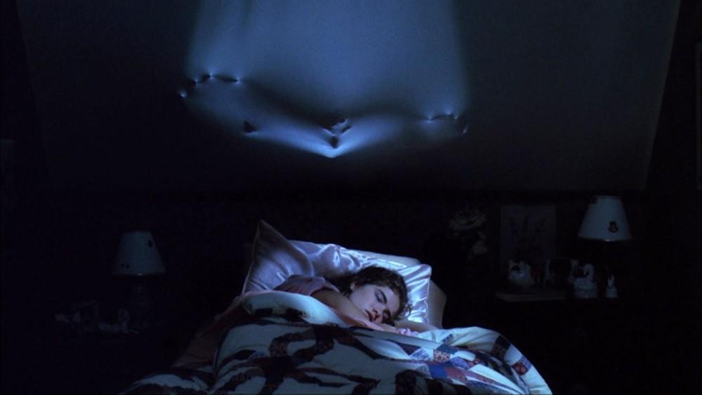 Texto alternativo: Cena do filme A Hora do Pesadelo. Fotografia retangular. Ao fundo, vemos um quarto com as luzes apagadas. Na parte superior, um vulto empurra a parede como se ela fosse um lençol. Na parte inferior, a personagem Nancy aparece dormindo.
