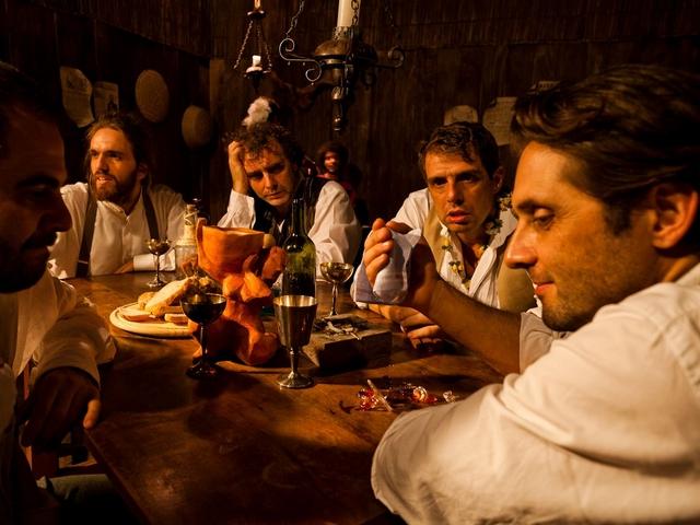 Cena do filme Noite na Taverna. Fotografia retangular. Ao fundo, vemos o ambiente noturno de uma taverna. Uma mesa com cinco homens ocupa toda a imagem. Os homens parecem dialogar, vestem roupas semelhantes e aparecem em poses diferentes. No centro da mesa, observamos uma garrafa de vinho, taças, uma escultura e outros objetos.