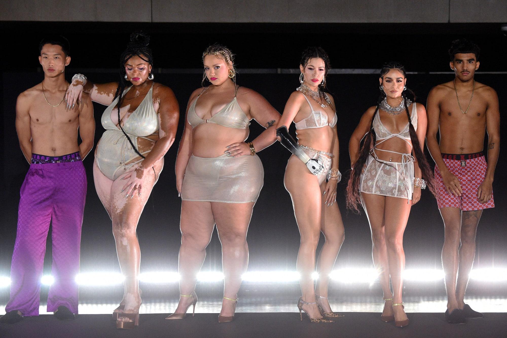 Cena do Savage X Fenty Vol. 3. Modelos posando durante o desfile, da esquerda para a direita: um homem asiatico magro usando uma calça roxa e sem camisa, uma mulher negra, gorda, com vitiligo usando box braids e um maiô prateado, uma modelo branca, gorda, loira usando um conjunto de sutiã e saia prateados, seguida por outra modelo branca, morena, com um braço robótico e usando um conjunto branco de calcinha e sutiã, a penúltima é a atriz Vanessa Hudgens, que é uma mulher branca, com tranças boxeadoras, usando um conjunto de sutiã e saia brancos e por último um modelo árabe, com um calção vermelho e rosa. Todos estão na frente de um fundo preto com uma luz horizontal branca na altura dos pés.