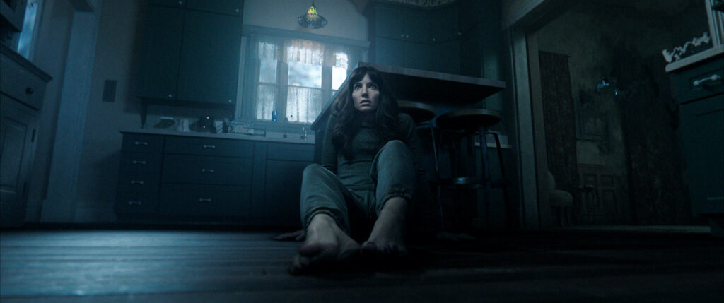 Cena do filme Maligno exibe uma mulher branca sentada no chão de uma cozinha. Ela está assustada com o que vê na sua frente. Suas costas estão encostadas num banquinho e ela está descalça. Tanto a calça quanto a blusa que ela veste são cinzas. A cozinha está escura, com pouca iluminação.