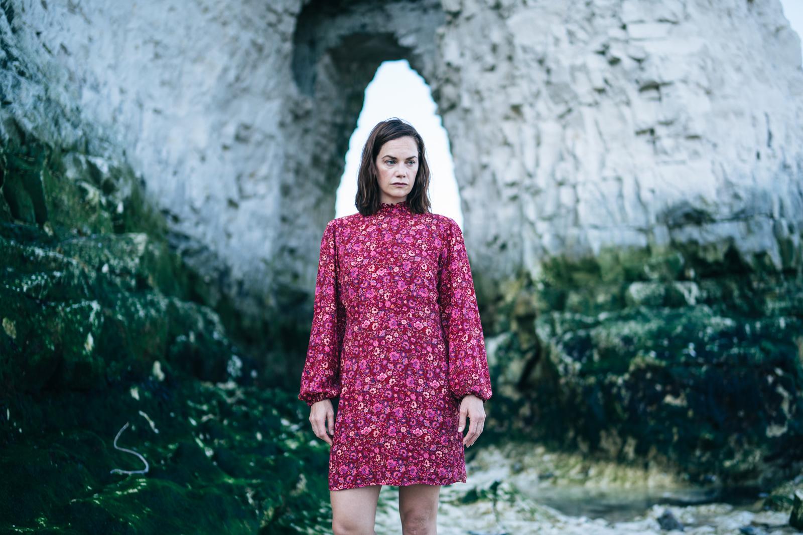 Cena do filme Coisas Verdadeiras, mostra uma mulher adulta branca de vestido vermelho em pé de dia. Ao seu redor, vemos moitas e um muro de pedra cinza.