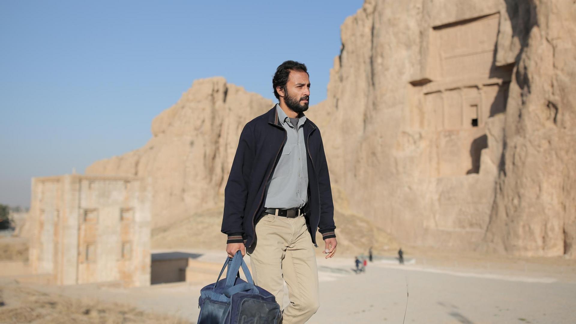 Cena do filme Um Herói. Mostra um homem adulto, iraniano, caminhando perto de uma montanha clara. Está de dia e está bem sol, e ele segura uma mala azul com a mão direita.