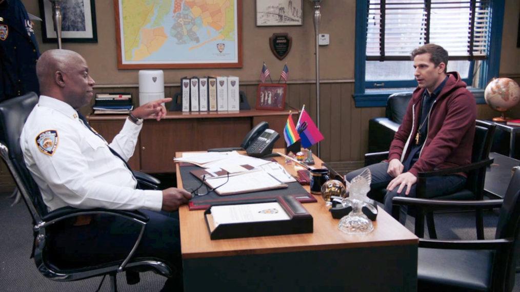 Cena da oitava temporada de Brooklyn Nine-Nine. A cena mostra o interior da sala do comandante Holt, sentado à mesa, que é um homem negro, idoso e usa camisa social branca. Do outro lado da mesa, está Jake Peralta, homem branco adulto que usa uma blusa vinho.