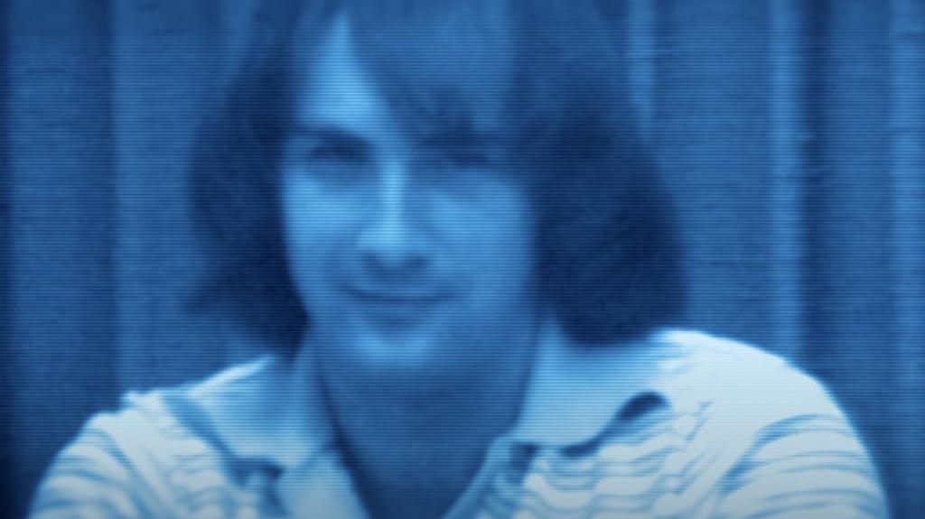 Cena da série As 24 Personalidades de Billy Milligan. A imagem mostra Billy do peito para cima; ele é um homem branco com cabelos cortados na altura dos ombros, usa uma camiseta polo de listras brancas, e sua expressão encara a câmera em desafio e desprezo. A imagem é na cor azul, e o fundo é uma cortina.