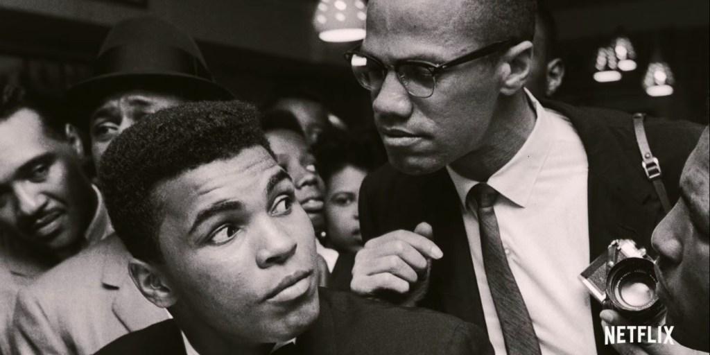 Cena do documentário Irmãos de Sangue. A imagem é preto e branca e Muhammad Ali está sentado com o pescoço virado para o lado, ouvindo Malcolm X que está atrás dele. Ali é um homem negro de cabelo crespo, está de terno preto e sua expressão é de curiosidade. Malcolm é um homem negro um pouco mais velho, com os cabelos cortados curtos e óculos, ele usa terno, camisa e gravata, e uma de suas mãos apoia no ombro de Ali, enquanto a outra segura uma pequena câmera; sua expressão é séria e ele está olhando para Ali. No fundo há diversos homens.
