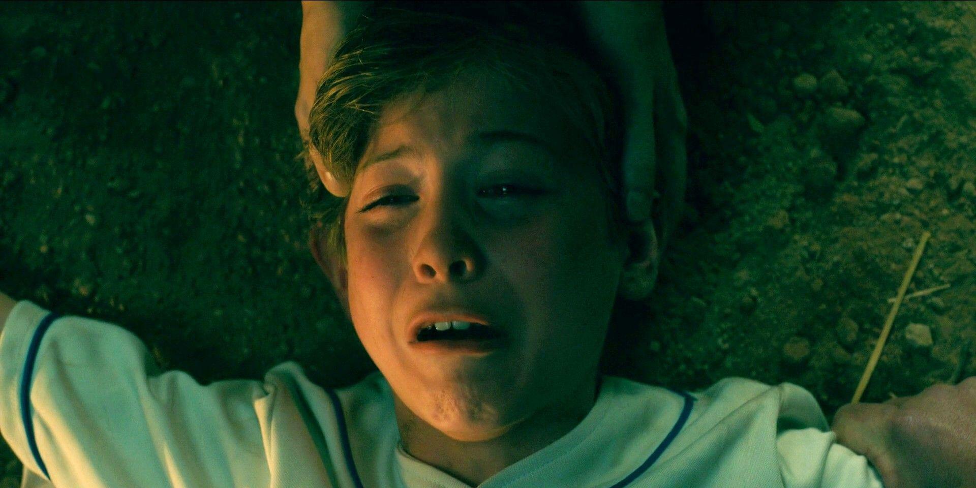 Cena do filme Doutor Sono. Um menino branco de cabelos loiros deitado no chão de terra vestindo uma blusa branca com detalhes azuis. Uma mão segura sua cabeça e seus braços. Sua expressão é de medo e pavor.