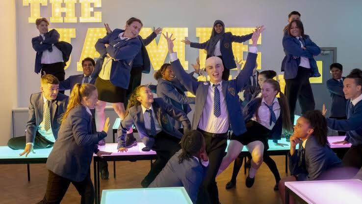 Cena de Todos Estão Falando sobre Jamie mostra um grupo de jovens performando de uniforme escolar em uma sala de aula.