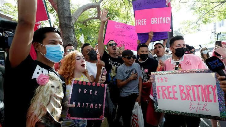 A imagem exibe um grupo de jovens segurando cartazes em um protesto pela liberdade tutelar da cantora Britney Spears.