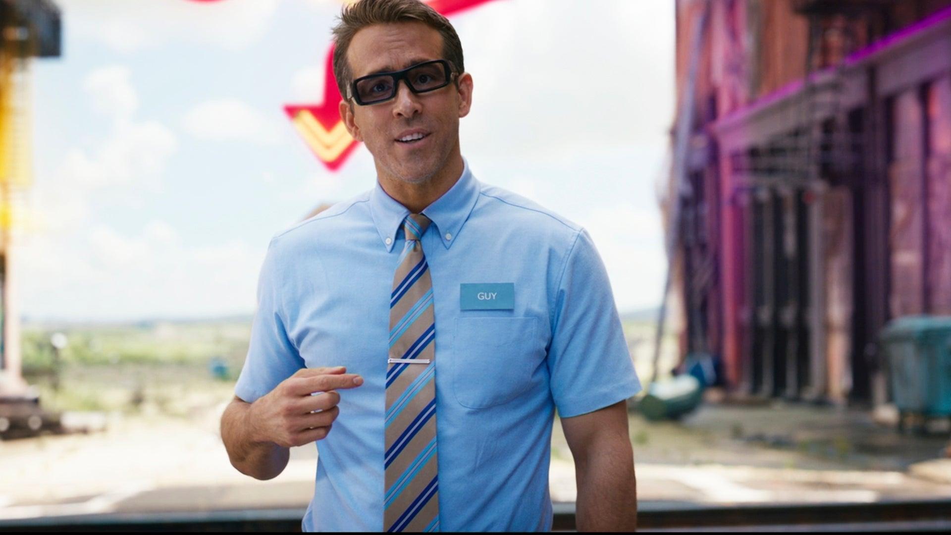 Cena do filme Free Guy em que Ryan Reynolds está ao centro. Ele é um homem branco de cabelos castanhos cortados com um ligeiro topete, usa óculos de armação preta, camisa social azul, gravata listrada de tons azuis e bege, e tem um crachá no peito. Sua expressão é abobada. Ao fundo há um horizonte com céu azul, e no canto direito há um prédio roxo.