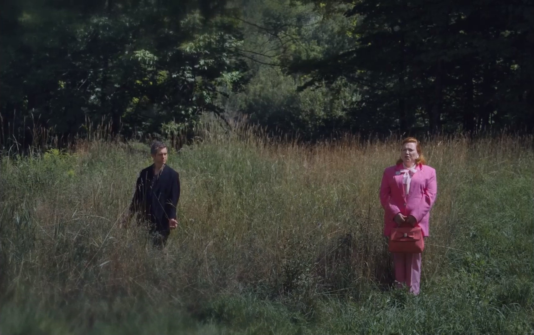 Cena do filme Higiene Social exibe um homem e uma mulher, brancos, parados no meio de uma grama alta. O homem, à esquerda, veste um terno preto e tem cabelo loiro curto. A mulher à direita, mais velha, tem cabelo ruivo comprido e veste um terno rosa. Carrega uma bolsa da mesma cor nas mãos.