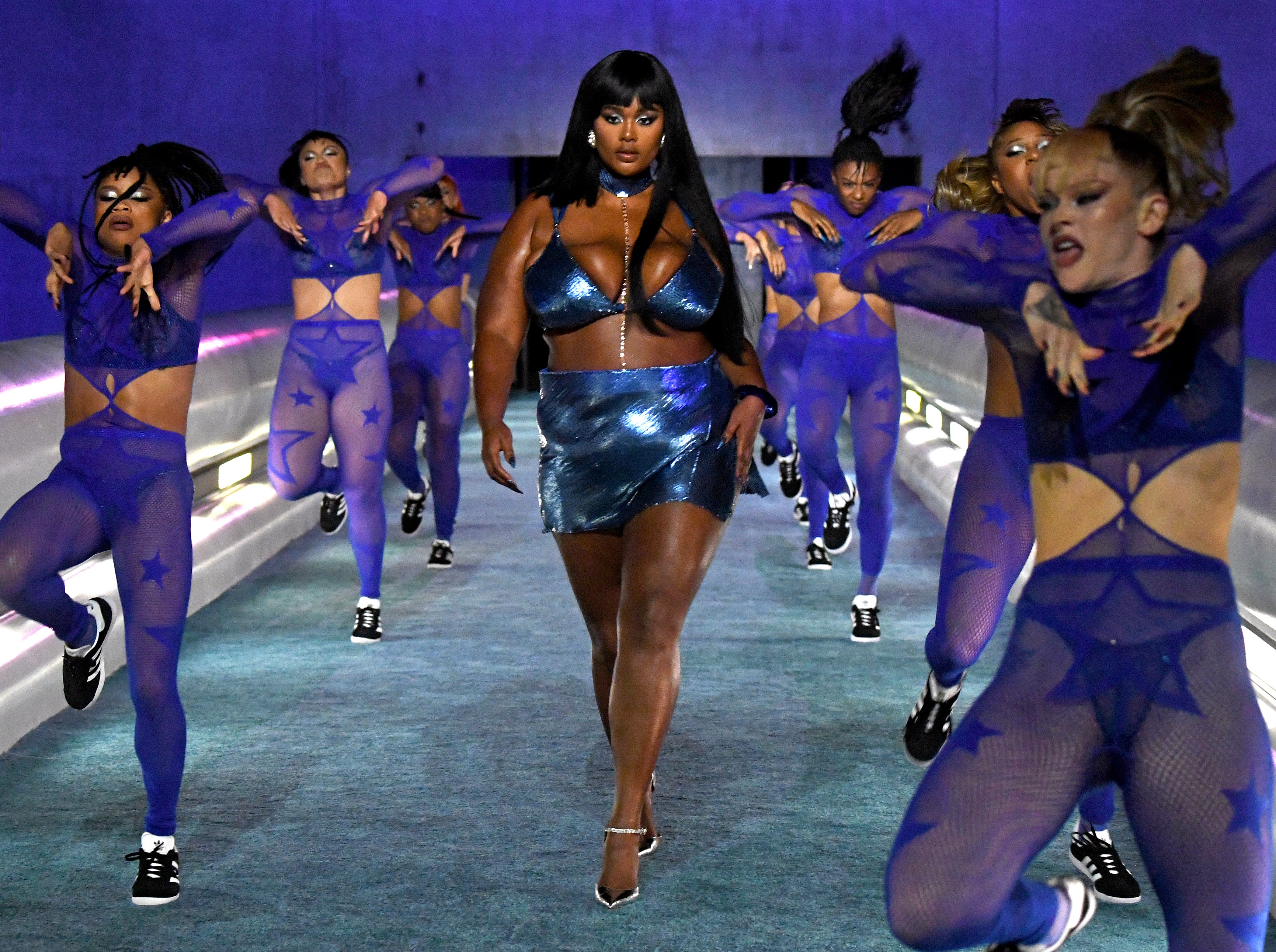 Cena do Fenty X Savage Show. Uma mulher negra, gorda, de cabelos pretos e grandes, usando um sutiã e saia azuis metálicos desfilando entre dez dançarinas, usando macacões azuis. Ao lado delas há corrimões e luzes azuis ao fundo.