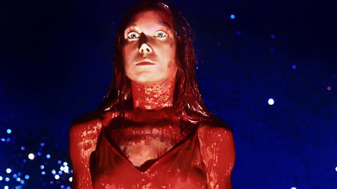 Cena do filme Carrie, a Estranha. Nesse cenário, a protagonista está no baile de formatura, que é decorado com um fundo azul e algumas luzes brancas. Na parte central está Carrie, com seus cabelos, roupas e corpo completamente banhados de sangue.
