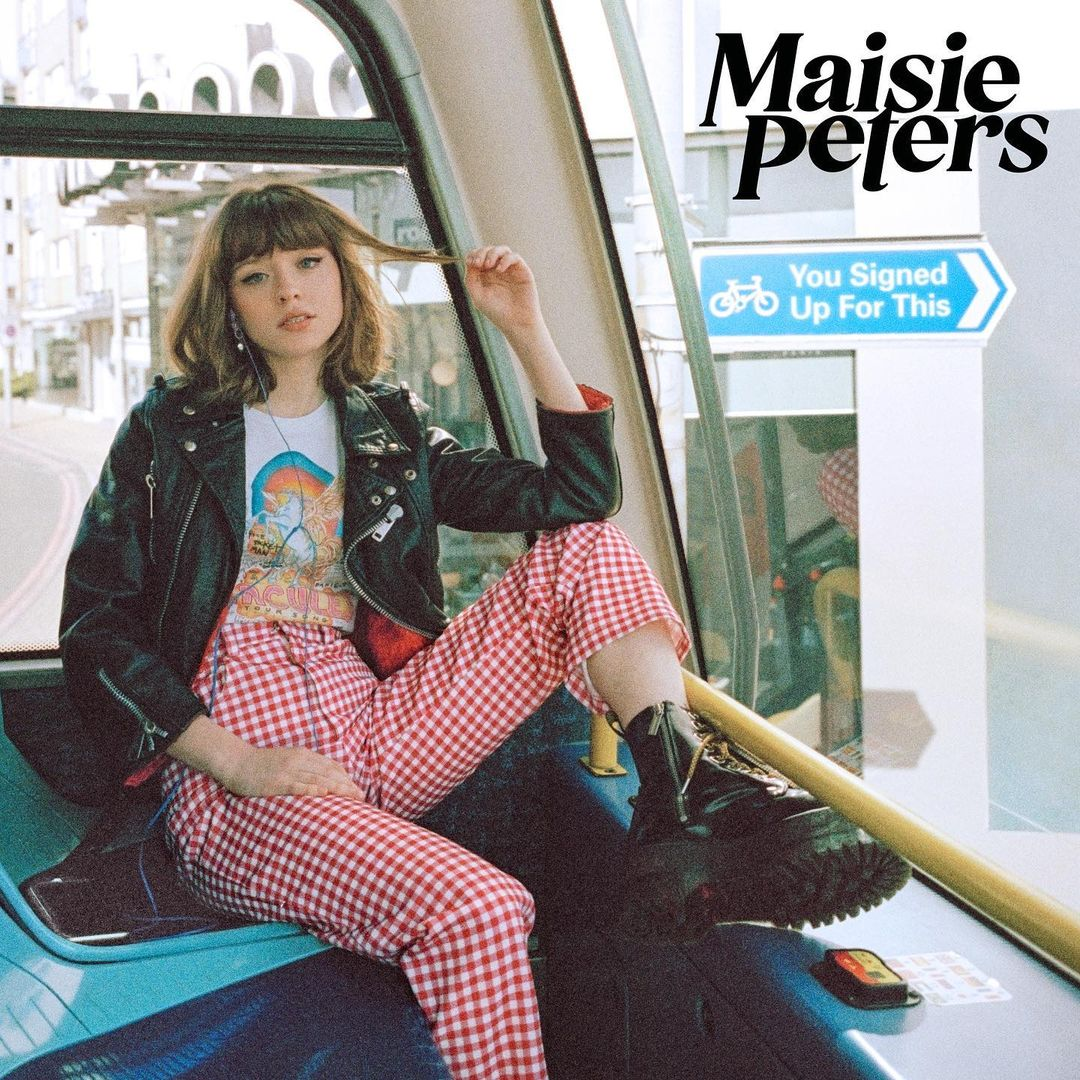 Capa do álbum You Signed Up For This - Maisie, jovem branca, magra e de olhos azuis, está sentada de forma despojada em um dos trens da cidade de Londres. Ela veste uma camisa branca com estampa de unicórnio, uma jaqueta de couro preto, uma calça xadrez branca e vermelha e uma bota de plataforma preta. Ela está usando fones de ouvido azul e uma de suas mãos segura uma mecha de seu cabelo castanho liso que vai até o ombro e cobre a testa com sua franja. Pela janela atrás dela podemos ver as ruas de Londres e uma placa de trânsito com o nome do álbum: You Signed Up For This. A imagem tem um efeito granulado como se tivesse sido tirada por uma câmera antiga.