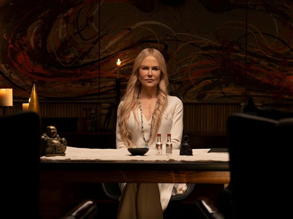 Cena de Nove Desconhecidos. Ao centro vemos Nicole Kidman, uma mulher branca, de cabelo loiro e longo. Ela veste um longo vestido branco e um colar de pedras azuis. Sua expressão facial é séria. À sua frente está uma mesa com toalha branca, nela tem uma tigela preta, duas garrafinhas transparentes de tampa vermelha e um peso de balança. À esquerda na mesa também há uma decoração sagrada. Mais a frente vemos dois encostos de cadeira desfocada. Atrás de Nicole vemos três velas acesas e uma pintura na parede de fundo verde e com traços laranja, branco e bordô