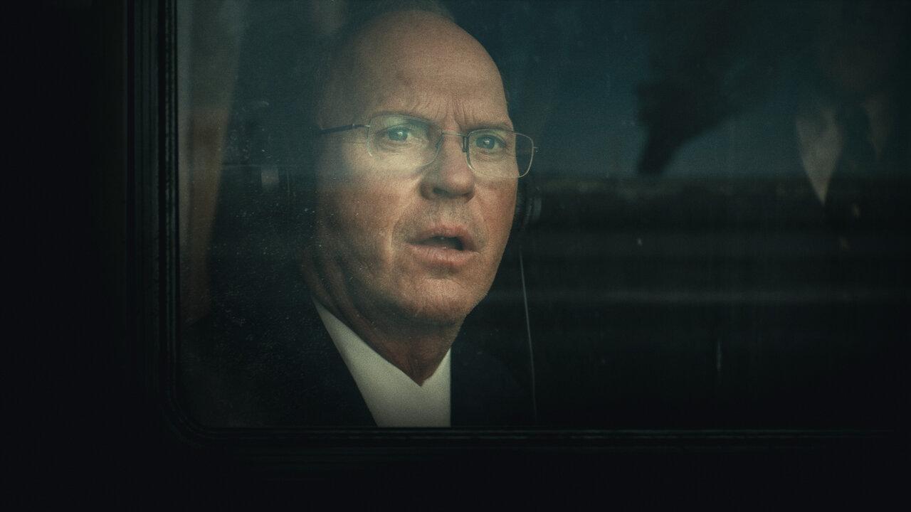Cena do filme Quanto Vale?. Nela vemos Michael Keaton, um homem branco e careca. Ele usa terno preto e camisa branca, óculos quadrado e um fone de ouvido de avião preto. Sua boca está aberta. Apenas seu busto está aparecendo e todo o resto da imagem é preto. Há um vidro entre a câmera que está filmando e o ator. Esse vidro é a janela do avião.