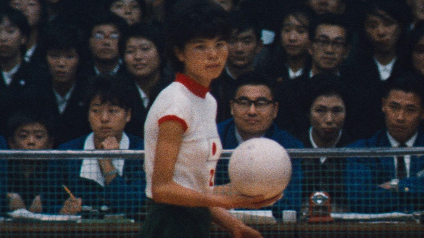 Cena do documentário As Bruxas do Oriente. A imagem mostra um momento de uma partida de voleibol. Ao centro, está uma jogadora japonesa de cabelos curtos pretos, vestindo o uniforme da esquipe que consiste numa camiseta branca de mangas e golas vermelhas e um short azul marinho. Ela segura a bola branca na mão direita, preparando-se para realizar um saque. Ao fundo, pode-se observar o público que acompanha a partida.