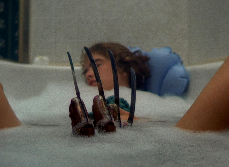 Cena do filme A Hora do Pesadelo. A imagem mostra a personagem Nancy, interpretada pela atriz Amanda Wyss, numa banheira de banho. Ela é uma jovem branca, loira, de cabelos curtos, e está apoada nas costas da banheira, de olhos fechados e com as pernas abertas. No meio, surge a luva de tesouras de Freddy Krueger,
