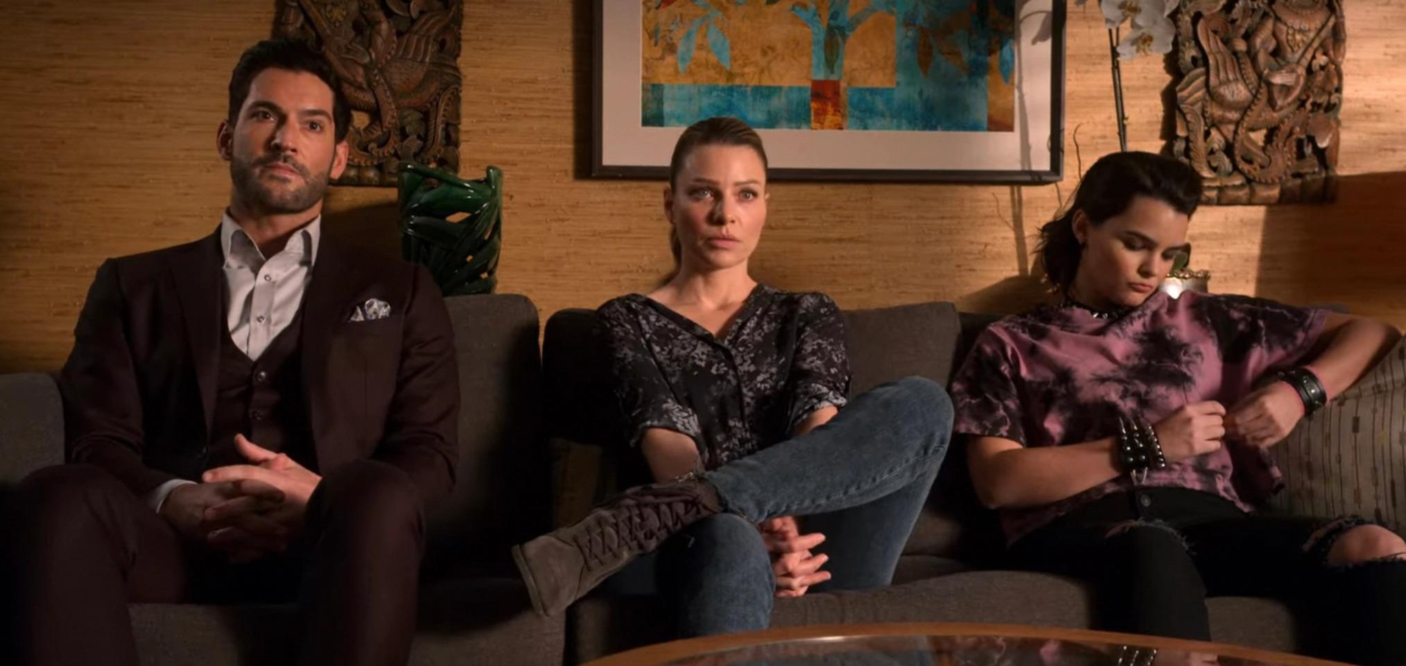 Cena da série Lúcifer em que Lúcifer, Chloe e Rory estão sentados nessa ordem em um sofá cinza. Lúcifer é um homem branco de cabelos pretos com topete e barba curtas, veste terno marrom e camisa branca, está com as mãos entrelaçadas no meio das pernas e tem expressão séria. À sua direita, Chloe está sentada com uma perna cruzada em cima da outra, as mãos entrelaçadas no meio das pernas e está encarando com irritação; ela é uma mulher branca de cabelos claros presos atrás da cabeça, usa camisa estampada em preto, calças jeans e botas marrons. No canto direito do sofá está Rory, sentada distraidamente e olhando para as mãos; ela é uma jovem branca de cabelos pretos curtos e lisos, usa camiseta em estampa roxa e preta, calças pretas com rasgos nos joelhos e acessórios com spikes no braço e pescoço. O fundo é uma sala de consultório com paredes em madeira clara, decorações em ferro e um quadro pendurados na parede.