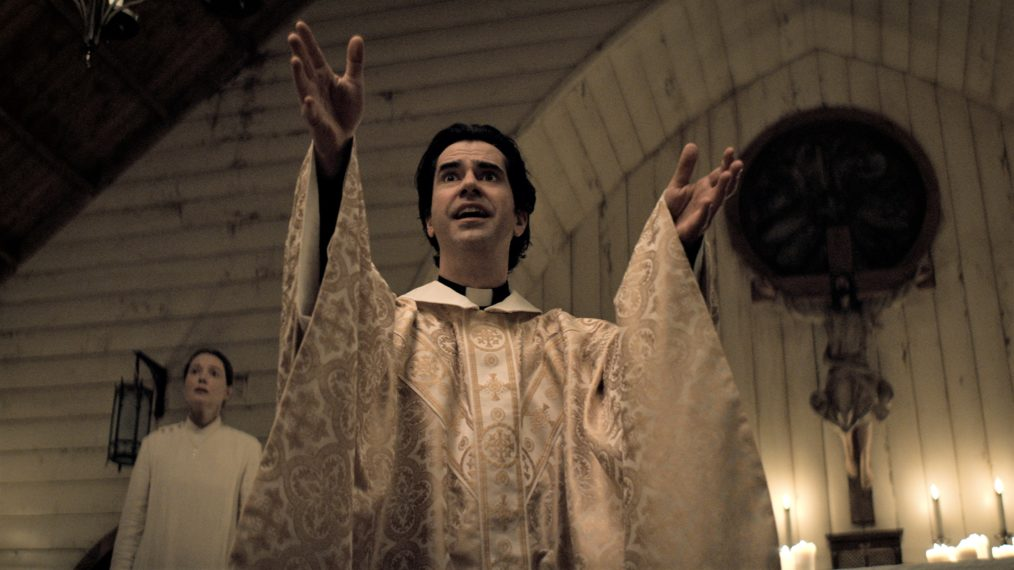 Cena da minissérie Missa da Meia-Noite. O Padre Paul (Hamish Linklater) prega um sermão acalorado no púlpito da capela. A câmera o encara de cima para baixo enquanto ele estende as mãos para frente, uma expressão exaltada no rosto. Atrás dele, à direita, a beata Bev Keane (Samantha Sloyan) encara estupefata o resto da igreja. Paul é caucasiano, possuí cabelos negros e curtos, usando uma túnica religiosa branca com detalhes dourados por cima do hábito. Bev também é caucasiana, de cabelos escuros puxados para trás, e usa um vestido plano e branco cobrindo o corpo todo, com três botões no ombro esquerdo. A igreja é construída com placas de madeira branca, com a pintura descascando. À esquerda do padre, a figura de Jesus crucificado, com algumas velas acesas dos lados. Uma janela circular acima da figura revela o céu noturno.