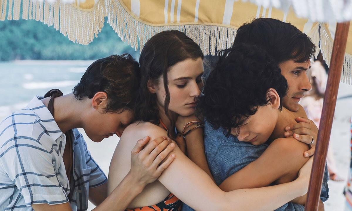 Cena do filme Tempo exibe uma família de pessoas brancas se abraçando embaixo de um guarda-sol em uma praia. A família é formada por um casal de um homem e uma mulher, e vemos um menino e uma menina, adolescentes.