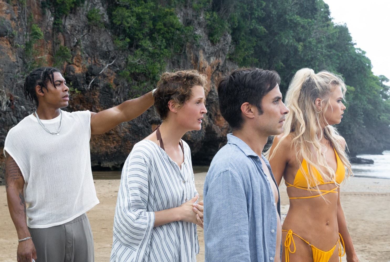 Cena do filme Tempo. A cena mostra 4 pessoas em uma praia de dia. Todos olham para o lado, em direção ao mar, com cara de medo.